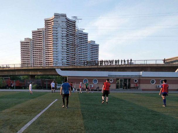 PHOTO: North Korean soldiers watch from an overpass as a group of foreigners play soccer on a field on Tongil Street, Pyongyang, North Korea, May 19, 2018. (Courtesy Alek Sigley)