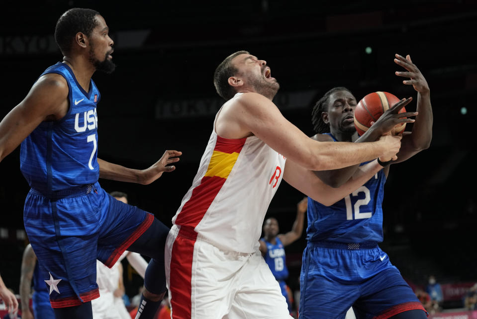 Spain's Marc Gasol (13), center, fights for a rebound with United States' Jrue Holiday (12), right, and Kevin Durant (7), left, during men's basketball quarterfinal game at the 2020 Summer Olympics, Tuesday, Aug. 3, 2021, in Saitama, Japan. (AP Photo/Eric Gay)