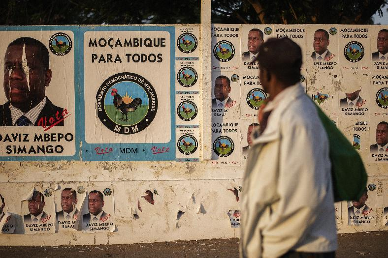 A man walks past a wall plastered with electoral posters for the Mozambican Democratic Movement presidential candidate Daviz Simango on October 9, 2014 in Maputo (AFP Photo/Gianluigi Guercia)