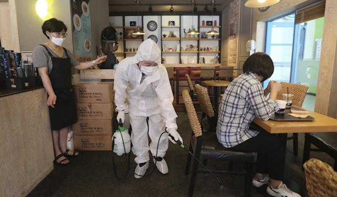 A health care worker carries out disinfection in a cafe in Goyang, which is part of the Seoul metropolitan area. Photo: AP