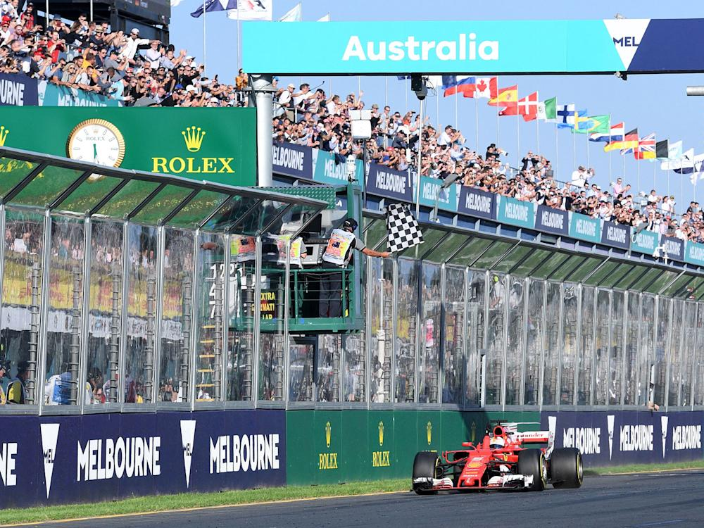 Sebastian Vettel crosses the line to win the Australian Grand Prix but a track invasion hindered his celebrations: Getty