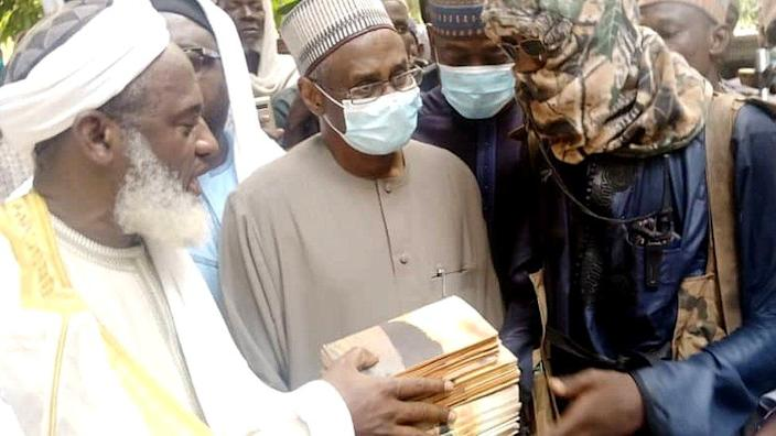 Sheikh Gumi handing a stack of books to a man in hood