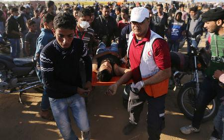 A Palestinian is evacuated during clashes with Israeli troops at the Gaza-Israel border at a protest demanding the right to return to their homeland, in the southern Gaza Strip March 31, 2018. REUTERS/Ibraheem Abu Mustafa
