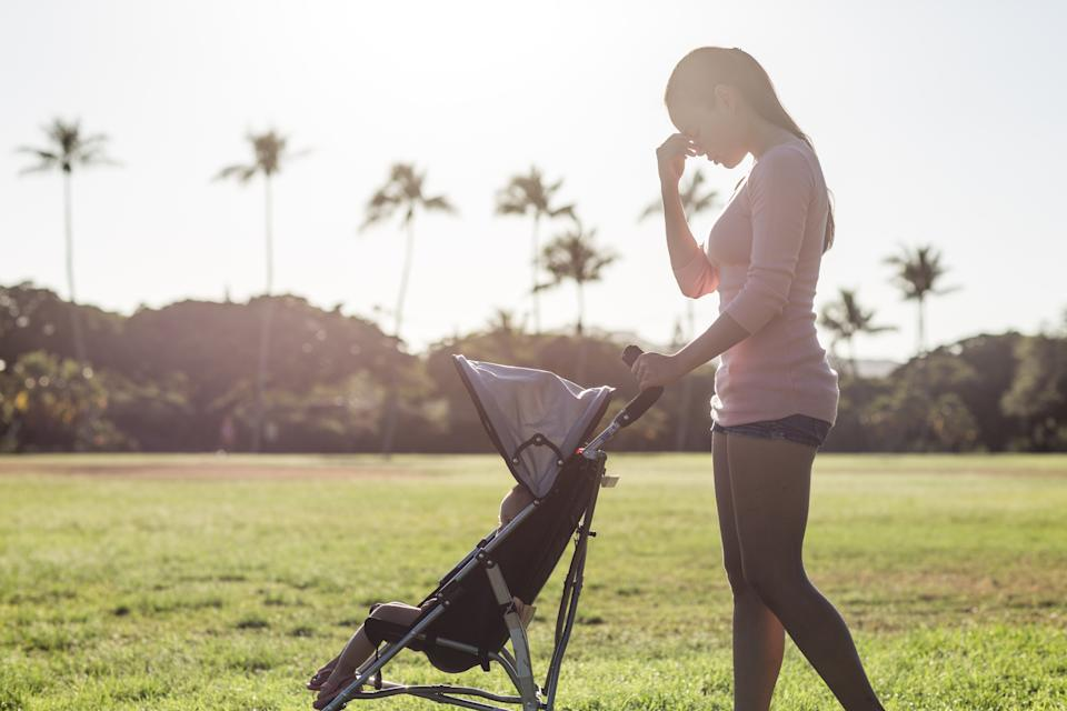 Sleepless single female parent with hand on her face. She is pushing a stroller with her baby child at the park during a sunny summer day. Maternity stress.