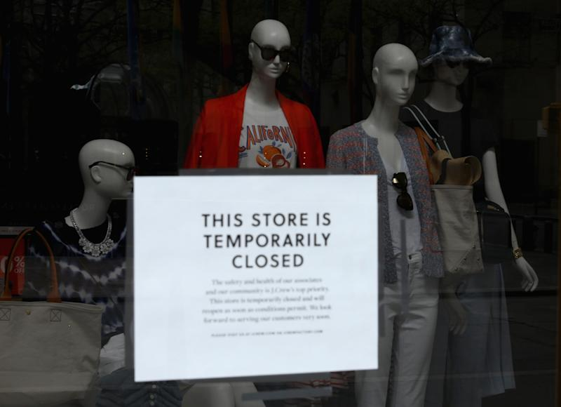 A sign is seen at the window of a closed J.Crew store near Rockefeller Plaza on May 4, 2020 in New York City. - US clothing retailer J. Crew filed to begin bankruptcy protection proceedings Monday, after reaching an agreement with major creditors on a $1.65 billion debt restructuring plan, the company said in a statement. The brand, whose clothes have been worn by former first lady Michelle Obama, said online sales operations, which account for more than half its revenues, will continue as normal. (Photo by Angela Weiss / AFP) (Photo by ANGELA WEISS/AFP via Getty Images)