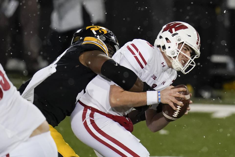 Wisconsin quarterback Graham Mertz is sacked by Iowa defensive lineman Chauncey Golston, left, during the second half of an NCAA college football game, Saturday, Dec. 12, 2020, in Iowa City, Iowa. Iowa won 28-7. (AP Photo/Charlie Neibergall)