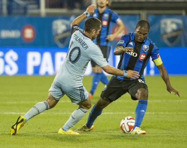 Sporting Kansas City's Benny Feilhaber rushes in to steal the ball from Montreal Impact's Patrice Bernier during the second half of a soccer game, Saturday, July 12, 2014 in Montreal. (AP Photo/The Canadian Press, Peter McCabe)