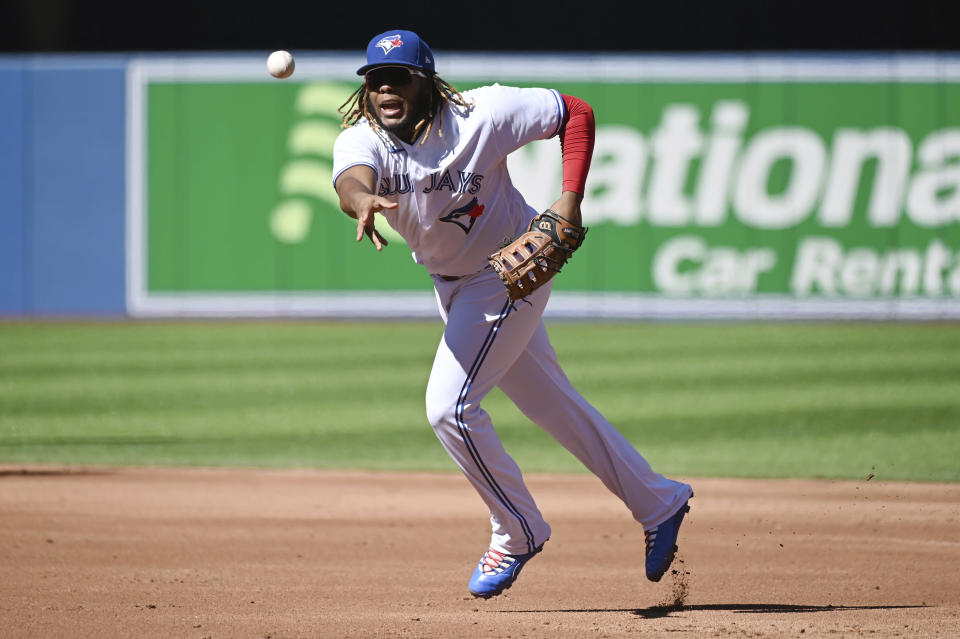 Toronto Blue Jays' Vladimir Guerrero Jr. tosses the ball to pitcher Jose Berrios at first base in the second inning of a baseball game against the Minnesota Twins in Toronto on Sunday, Sept. 19, 2021. Berrios mishandled the throw and Minnesota Twins' Nick Gordon was safe at first base. (Jon Blacker/The Canadian Press via AP)