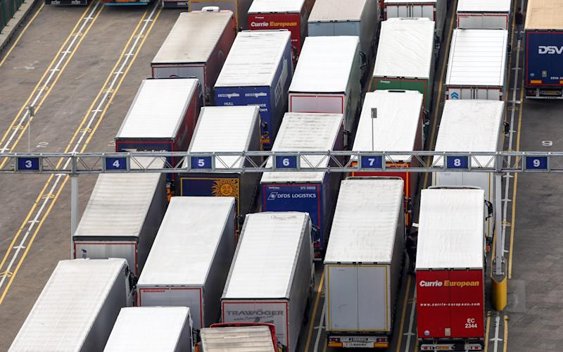 Lorries stand in line while waiting to board a ferry at the port of Dover - Bloomberg