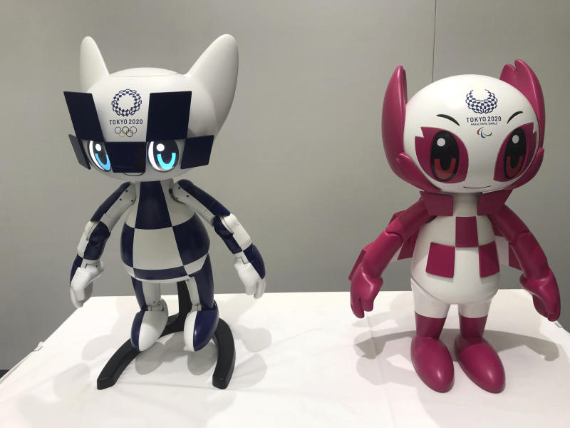 """In this Thursday, July 18, 2019, photo, robots of mascots of Olympics """"Miraitowa,"""" left, and Paralympics """"Someity"""" are shown to the media at Toyota Motor Corp. headquarters in Tokyo. The mascot robots' eyes change to the images of stars and hearts. The Japanese automaker Toyota, a major Olympic sponsor, is readying various robots for next year's Tokyo Olympics. (AP Photo/Yuri Kageyama)"""