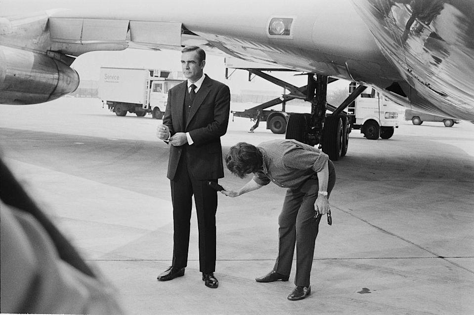 <p>Sean Connery in-between scenes on the set of <em>Diamonds Are Forever</em> in 1971. While filming at an airfield, the actor's suit is attended to by an assistant.</p>