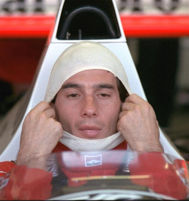 FILE - In this November 4, 1989, file photo, Brazilian driver Ayrton Senna, in a McLaren Honda, pulls on a fire resistant mask before going out to practice for the Australian Grand Prix. Senna won three Formula One titles in 1988, 1990 and '91 all with McLaren. He moved to the Williams team for his tragic 1994 season. Despite his career being cut short when he was 34, his 41 wins stand third all-time behind Michael Schumacher's 91 and rival Alain Prost's 51. He died at the 1994 San Marino Grand Prix. (AP Photo/Stephan Holland, File)