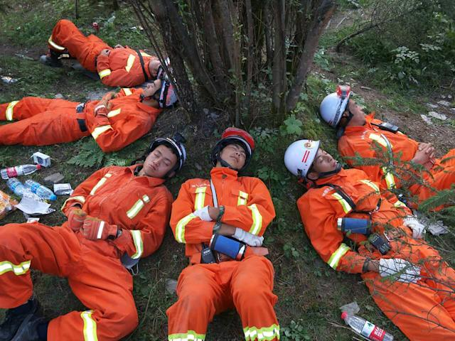 <p>Chinese paramilitary police sleep on the ground after an 18-hour rescue operation in Jiuzhaigou in China's southwestern Sichuan province on Aug. 9, 2017. (Photo: STR/AFP/Getty Images) </p>