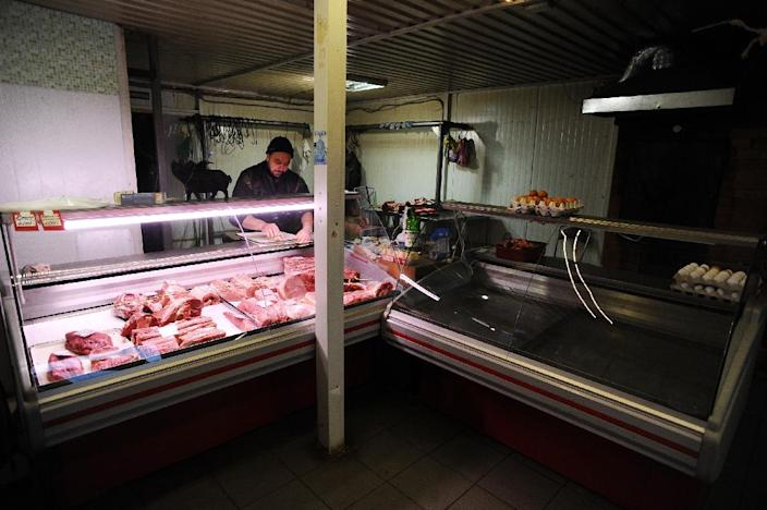 """Stanislav Kushevich, pictured in his butcher's shop, says: """"Putin is a good man, but what can he do? It's too complicated, the country is too big, and corruption is everywhere."""" (AFP Photo/Olga Maltseva)"""