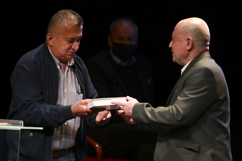 Armando Acuña, left, a former city councilman who was kidnapped by the Revolutionary Armed Forces of Colombia, FARC, is handed a book of the peace accords by former FARC commander Carlos Antonio Lozada, during an event at the Truth Commission to commemorate victims of the country's decades-long armed conflict, in Bogota, Colombia, Wednesday, June 23, 2021. (AP Photo/Ivan Valencia)