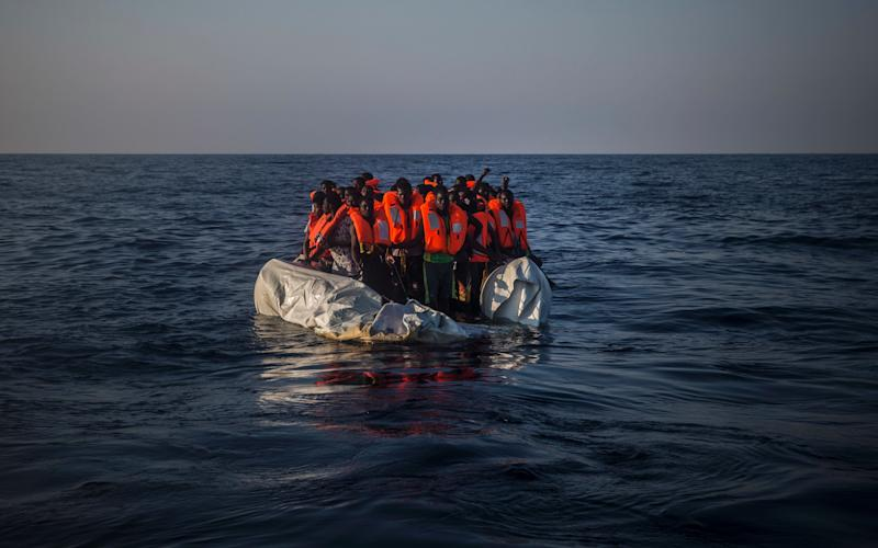 Migrants wait aboard a partially punctured rubber boat during a rescue operation on the Mediterranean Sea - Copyright 2016 The Associated Press. All rights reserved.