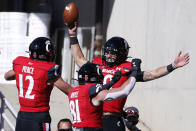 FILE - In this Saturday, Oct. 31, 2020, file photo, Cincinnati quarterback Desmond Ridder, rear, celebrates a touchdown with teammates Alec Pierce (12) and Cam Jones (18) during the first half of an NCAA college football game against Memphis in Cincinnati. An unusual college football season has produced some unexpected unbeaten teams dotting the AP Top 25 with about a month left. Led by No. 7 Cincinnati and No. 8 BYU, five teams from outside the Power Five conferences have yet to lose. (AP Photo/Gary Landers, File)