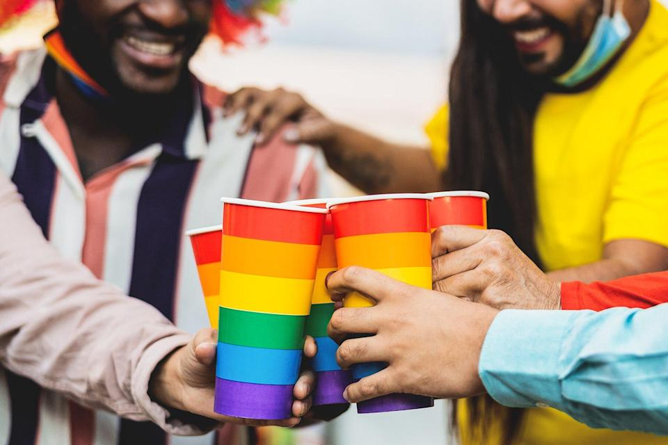 People cheering and drinking cocktails in gay pride festival event