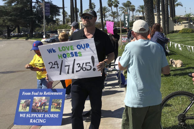 Kentucky Derby-winning trainer Doug ONeill, center, holds a sign during a rally in support of horse racing and its workers outside the main gate at Santa Anita Park in Arcadia, Calif on Saturday, Oct. 5, 2019. (AP Photo/Beth Harris)