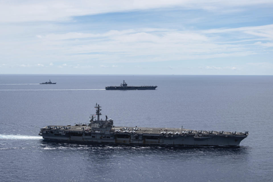 In this photo provided by U.S. Navy, the USS Ronald Reagan (CVN 76, front) and USS Nimitz (CVN 68, rear) Carrier Strike Groups sail together in formation, in the South China Sea, Monday, July 6, 2020. China on Monday, July 6, accused the U.S. of flexing its military muscles in the South China Sea by conducting joint exercises with two U.S. aircraft carrier groups in the strategic waterway.(Mass Communication Specialist 3rd Class Jason Tarleton/U.S. Navy via AP)