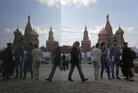 People are seen in a reflection as they gather near St. Basil's Cathedral (R) and the Kremlin in central Moscow, April 29, 2014. REUTERS/Maxim Shemetov