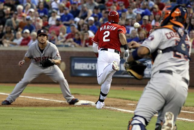 Houston Astros first baseman Brett Wallace (29) waits for the throw from catcher Carlos Corporan, right, as Texas Rangers' Leonys Martin (2) sprints to the bag on a bunt single in the third inning of a baseball game Monday, Aug. 19, 2013, in Arlington, Texas. (AP Photo/Tony Gutierrez)