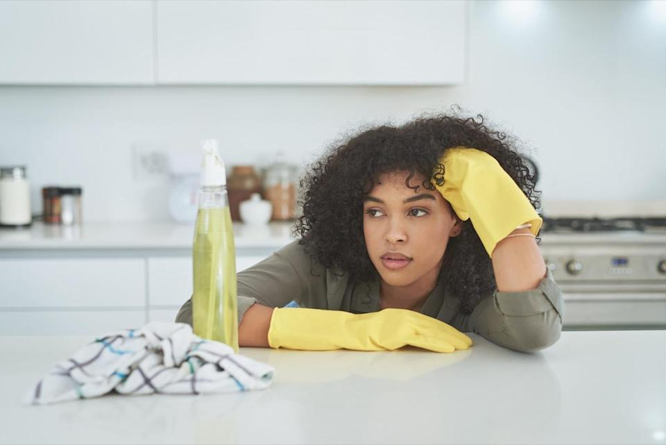 Shot of a young woman looking tired while cleaning a kitchen counter at home