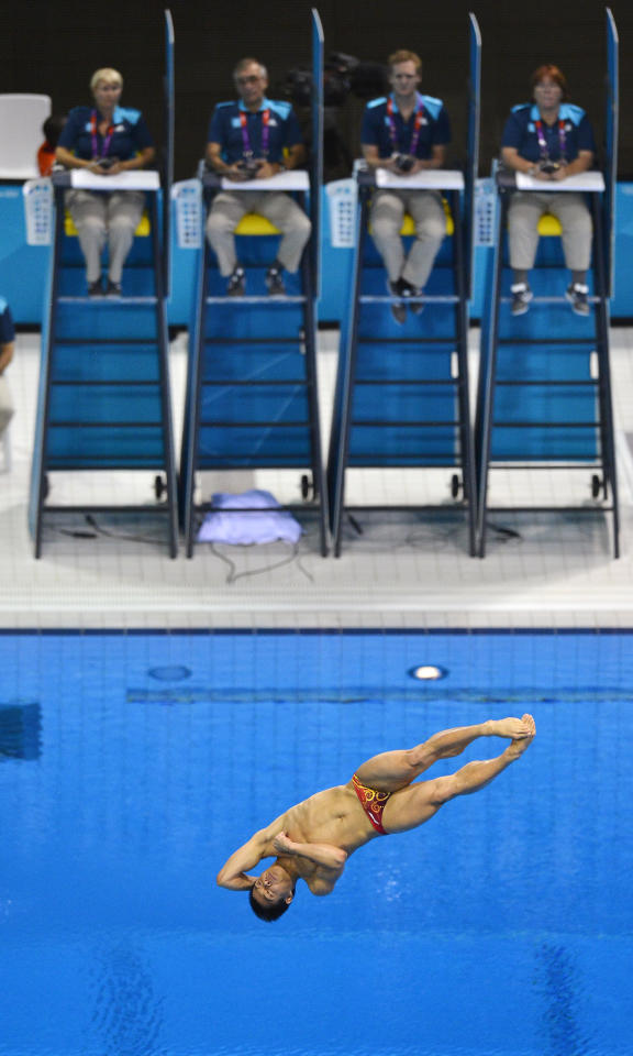 Judges watch as China's He Chong performs a dive during the men's 3m springboard preliminary round at the London 2012 Olympic Games at the Aquatics Centre August 6, 2012.     REUTERS/Toby Melville (BRITAIN  - Tags: SPORT DIVING OLYMPICS SPORT SWIMMING)