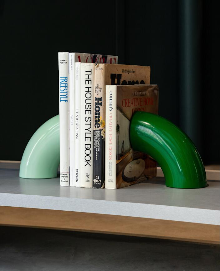 """<div class=""""caption""""> The Tubo bookends by <a href=""""https://biritestudio.com/collections/objects2/products/tubo-bookends"""" rel=""""nofollow noopener"""" target=""""_blank"""" data-ylk=""""slk:Bi-Rite Studio"""" class=""""link rapid-noclick-resp"""">Bi-Rite Studio</a> house some of Telsha's favorite reading materials. A longtime collector of pre-owned books, Telsha turns to <a href=""""https://www.shopmilg.com/"""" rel=""""nofollow noopener"""" target=""""_blank"""" data-ylk=""""slk:MILG"""" class=""""link rapid-noclick-resp"""">MILG</a> to source many out-of-print gems. </div> <cite class=""""credit"""">Photo by Justin Boone</cite>"""