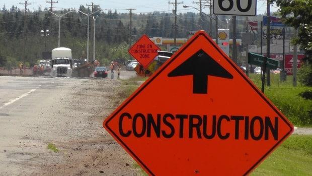 An orange sign indicates construction, with a sign in the distance indicating a construction zone. RCMP say a car travelling on Highway 101 had slowed down when it entered a construction zone but was struck from behind by an SUV. (Pat Martel/CBC - image credit)