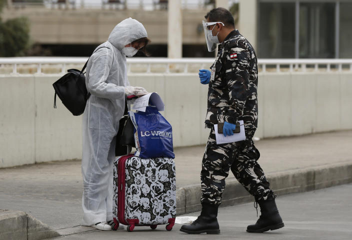 A Lebanese passenger who was stuck in Saudi Arabia is asked by a Lebanese policemen to show her documents in a parking lot at Rafik Hariri Airport, in Beirut, Lebanon, Sunday, April 5, 2020. A jet carrying more than 70 Lebanese citizens, who had been stuck in Saudi Arabia after Beirut's international airport closed nearly three weeks ago to limit the spread of coronavirus, arrived in Lebanon Sunday. The flight was the beginning of flights that aim to return thousands of Lebanese from around the world. (AP Photo/Hussein Malla)