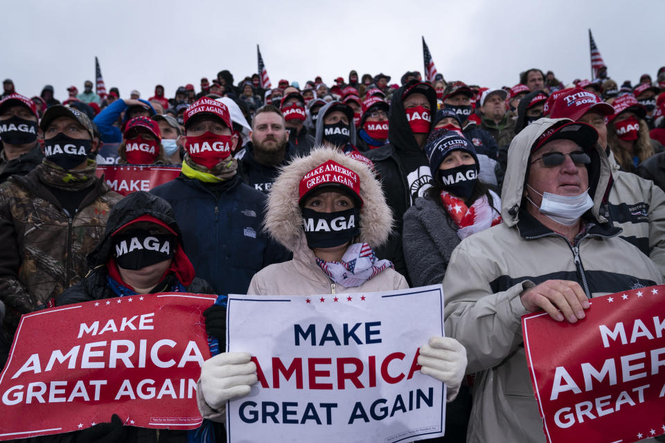Supporters listen as President Donald Trump speaks during a campaign rally at Capital Region International Airport, Tuesday, Oct. 27, 2020, in Lansing, Mich. (AP Photo/Evan Vucci)