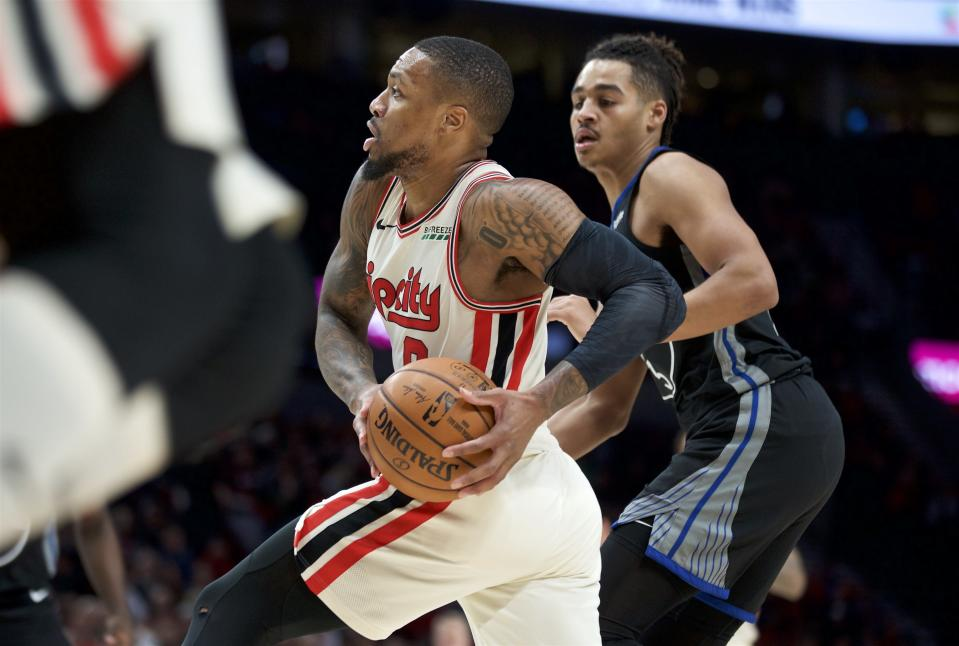 Portland Trail Blazers guard Damian Lillard drives to the basket past Golden State Warriors guard Jordan Poole during the first half of an NBA basketball game in Portland, Ore., Wednesday, Dec. 18, 2019. (AP Photo/Craig Mitchelldyer)