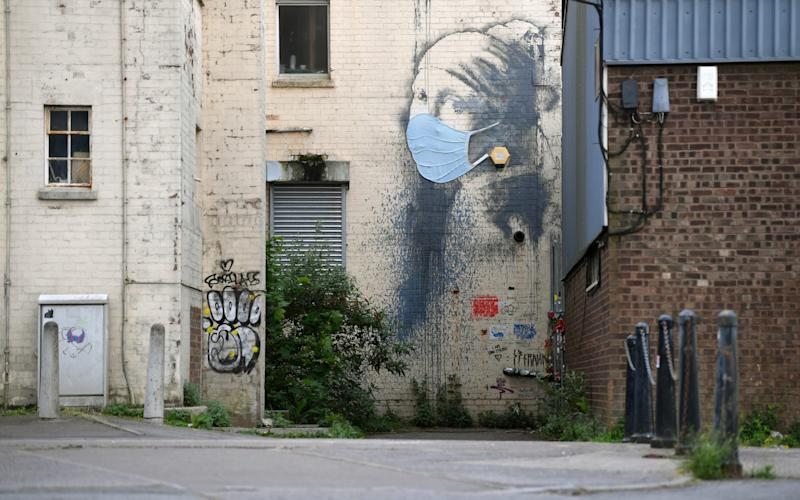 The graffiti artwork by Banksy named 'Girl with a Pierced Eardrum' is seen with a protective face mask at Hannover Place on April 27, 2020 in Bristol, England. British Prime Minister Boris Johnson, who returned to Downing Street this week after recovering from Covid-19, said the country needed to continue its lockdown measures to avoid a second spike in infections.  - Dan Mullan/Getty Images Europe