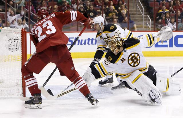 Phoenix Coyotes' Oliver Ekman-Larsson (23), of Sweden, scores a goal against Boston Bruins' Tuukka Rask (40), of Finland, as Bruins' Zdeno Chara (33), of the Czech Republic, arrives late to defend during the second period of an NHL hockey game on Saturday, March 22, 2014, in Glendale, Ariz. (AP Photo/Ross D. Franklin)