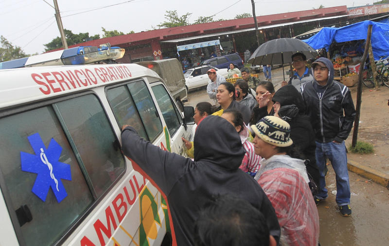 Inmates relatives surround an ambulance leaving the Palmasola jail in Santa Cruz, Bolivia, Friday, Aug. 23, 2013. At least 15 inmates were killed, many in a fire, early Friday in a battle among inmates for control of part of an overcrowded maximum-security prison in Bolivia's eastern lowlands, according to National Police Chief Alberto Aracena. (AP Photo)