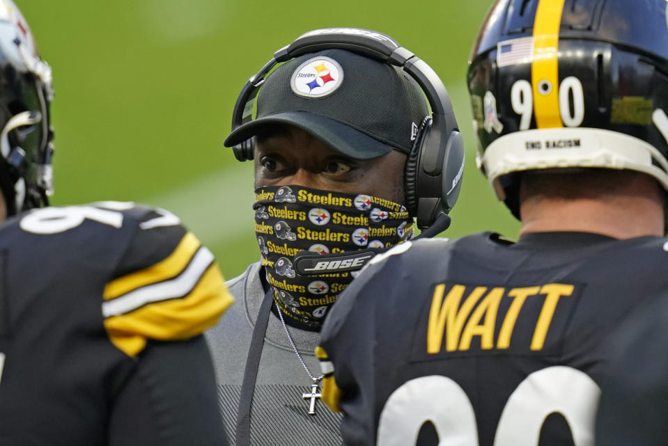 Pittsburgh Steelers head coach Mike Tomlin, center, wears a mask as he talks to players on the sideline. (AP Photo/Keith Srakocic)