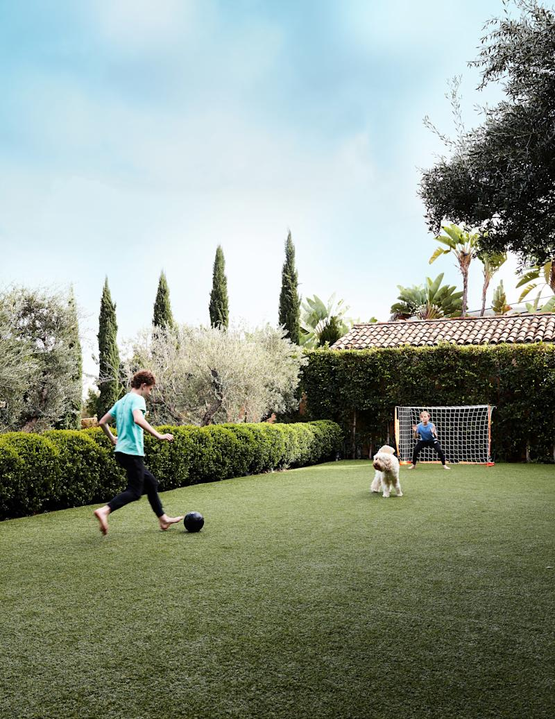 Miles (left) and Henry play soccer in the garden.