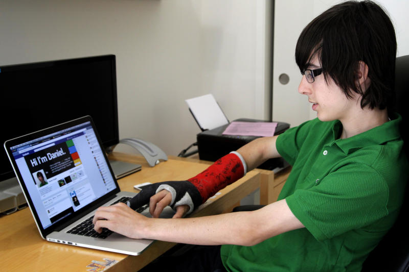 """This Monday, March 25, 2013 photo, shows  Daniel Singer, 13. working at his computer in Los Angeles. Singer,  thinks the average teenager wants to see new stuff on facebook. Singer says, Facebook is part of a daily routine. """"Kind of like brushing your teeth,"""" he says.   (AP Photo/Nick Ut)"""