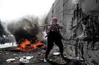 A Palestinian demonstrater uses an axe to try and destroy a part of the Israeli separation wall separating the West Bank city of Abu Dis from east Jerusalem, during clashes with Israeli security forces on November 2, 2015 (AFP Photo/Ahmad Gharabli)