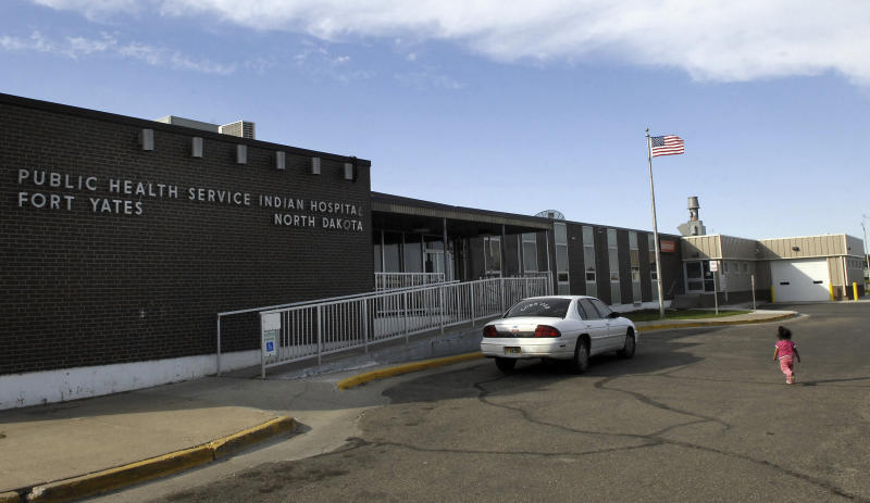 FILE - In this Oct. 14, 2008, a small child walks toward the front door of the Public Health Service Indian Hospital on the Standing Rock Reservation in Fort Yates. N.D.  A federal audit released Monday, July 22, 2019, finds that government hospitals placed Native Americans at increased risk for opioid abuse and overdoses. The audit says a handful of Indian Health Service hospitals, including the Fort Yates Hospital, failed to follow the agency's protocols for dispensing and prescribing the drug. The Indian Health Service agreed with the more than a dozen recommendations and says changes are in the works. (AP Photo/Will Kincaid, File)