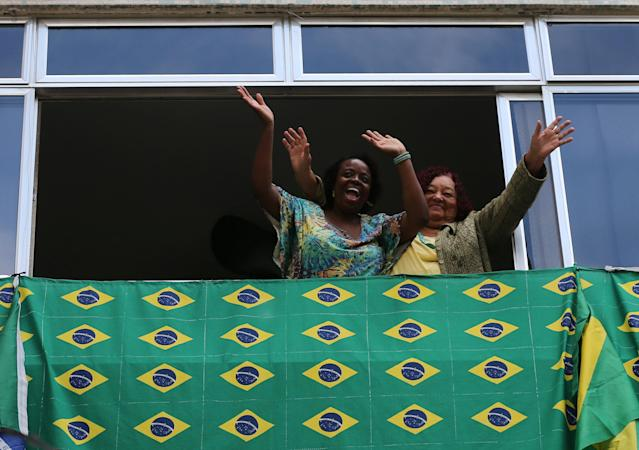Fans wave from a window before the World Cup Group E soccer match between Brazil and Switzerland, in Rio de Janeiro, Brazil June 17, 2018. REUTERS/Sergio Moraes