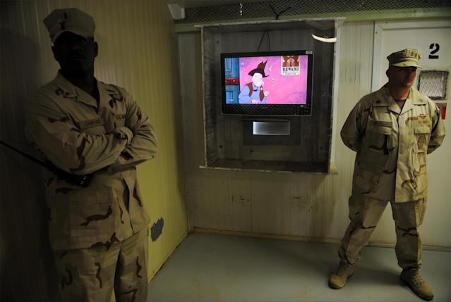 """GUANTANAMO BAY, CUBA - DECEMBER 10: An image reviewed by the U.S. military shows guards in the movie room at the """"Camp Four"""" detention facility during a visit by journalists December 10, 2008 on U.S. Naval Station Guantanamo Bay, Cuba. Camp Four houses the most compliant detainees where they live in a more open, community oriented manner. National Geographic programs and cartoons are popular with detainees. (Photo by Mandel Ngan-Pool/Getty Images)"""