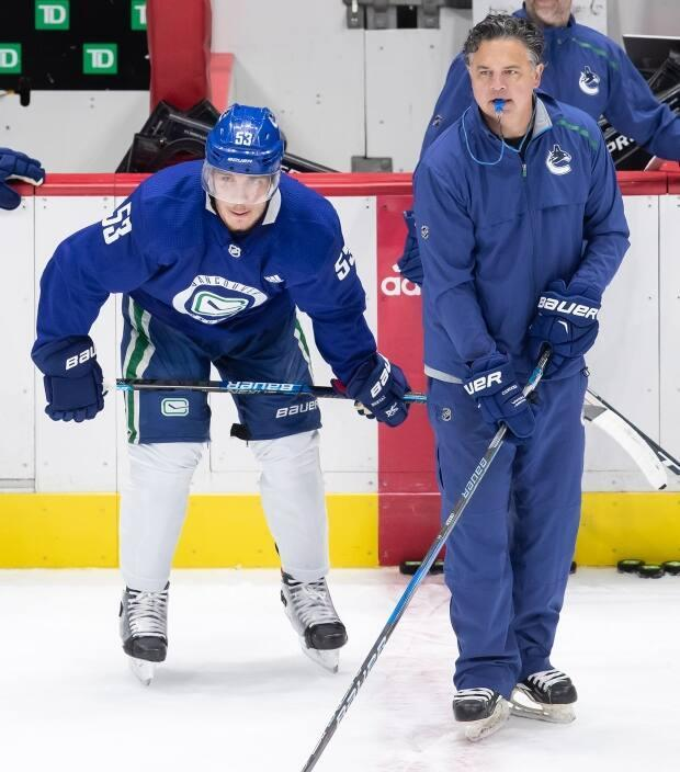 Vancouver Canucks captain Bo Horvat, left, stands beside head coach Travis Green. Both contracted COVID-19 in the outbreak that hit the team.  (Darryl Dyck/The Canadian Press - image credit)