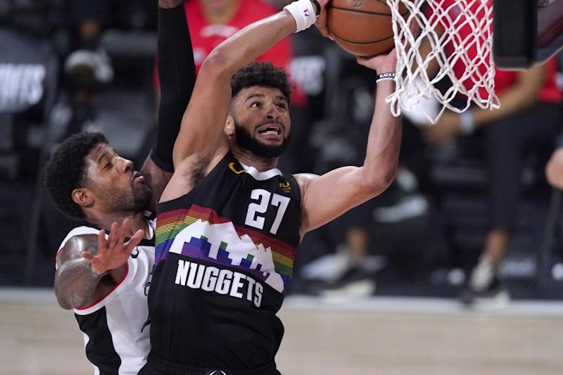 Denver Nuggets' Jamal Murray (27) goes up for a shot as Los Angeles Clippers' Paul George defends during the second half of an NBA conference semifinal playoff basketball game Sunday, Sept. 13, 2020, in Lake Buena Vista, Fla. (AP Photo/Mark J. Terrill)
