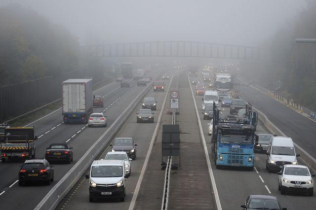 Traffic makes it's way through dense fog between junctions 4 and 3 of the M3 Motorway in near to Frimley in Hampshire PRESS ASSOCIATION Photo. Picture date: Monday November 2, 2015. See PA story WEATHER . Photo credit should read: Andrew Matthews/PA Wire