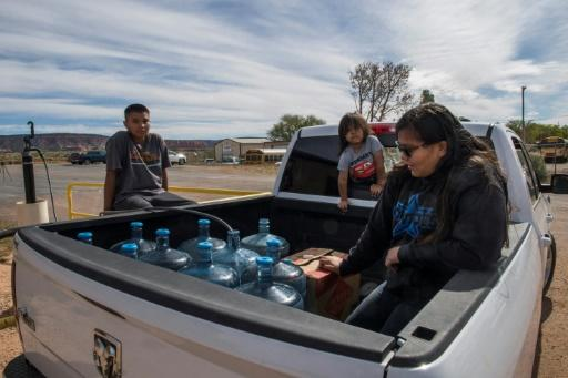 Members of the Larson family who have no running water in their home, collect water from a distribution point in the Navajo Nation town of Thoreau