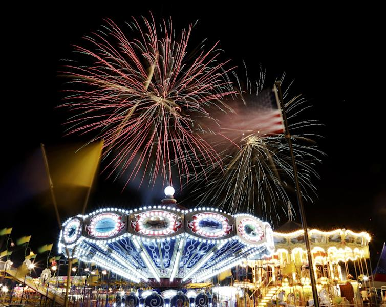 A United States flag waves next to carnival rides as fireworks burst in the air during the Fourth of July Independence Day show at State Fair Meadowlands, Tuesday, July 3, 2012, in East Rutherford, N.J. (AP Photo/Julio Cortez)