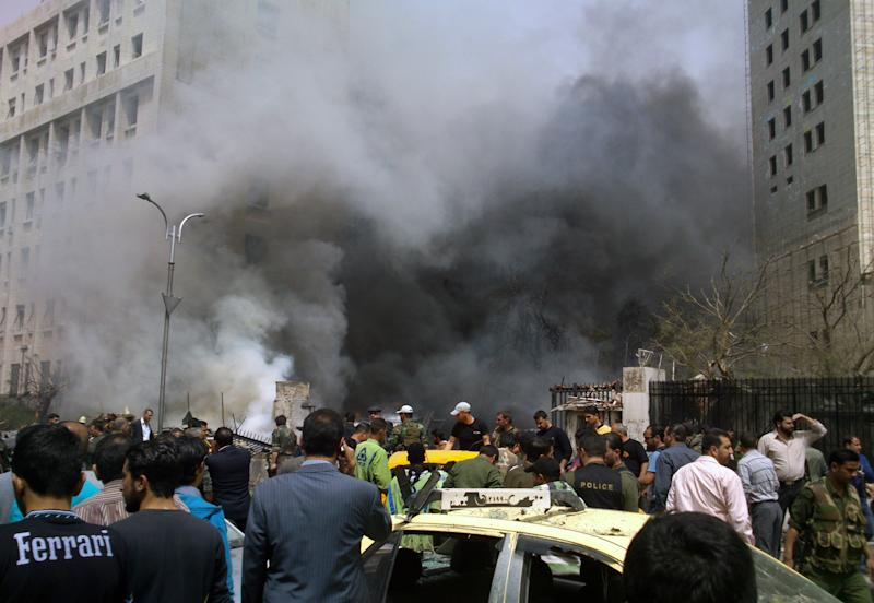 This photo released by the Syrian official news agency SANA, shows smoke rising from burned cars after a huge explosion shook the Sabaa Bahrat Square, one of the capital's biggest roundabouts, in Damascus, Syria, Monday, April. 8, 2013. A car bomb rocked a busy residential and commercial district in central Damascus on Monday, killing more than a dozen with many more injured and sending a huge cloud of black smoke billowing over the capital's skyline, Syrian state-run media said. (AP Photo/SANA)