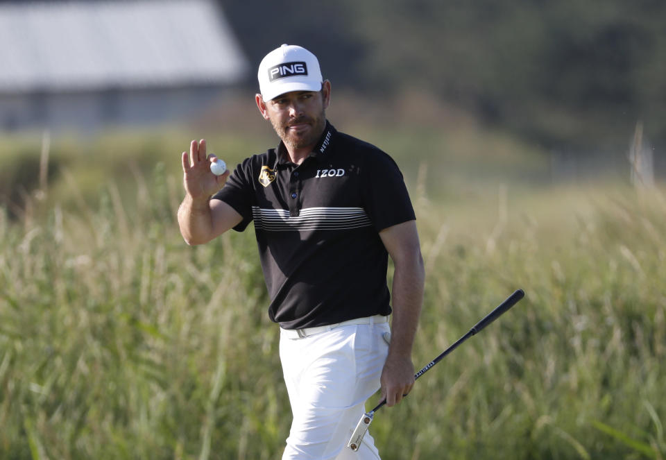 South Africa's Louis Oosthuizen acknowledges the crowd after putting an eagle on the 14th green during the second round of the British Open Golf Championship at Royal St George's golf course Sandwich, England, Friday, July 16, 2021. (AP Photo/Peter Morrison)